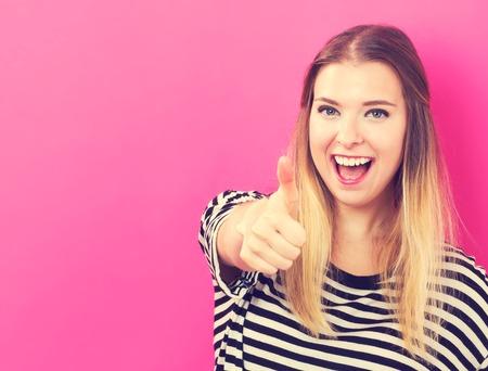 Šťastná mladá žena dává palec na růžové pozadí