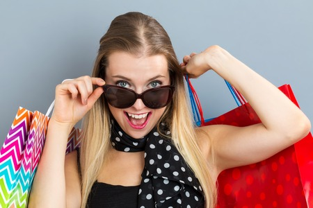 woman bag: Happy young woman holding many shopping bags on a gray background