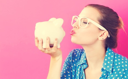 money background: Young woman with a piggy bank on pink background