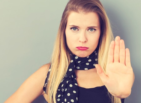 rejection: Young woman making a rejection pose on a gray background