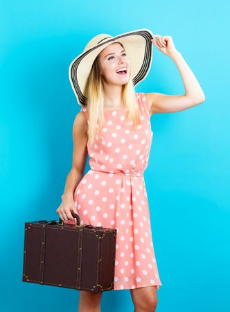 woman young: Happy young traveling woman on blue background Stock Photo