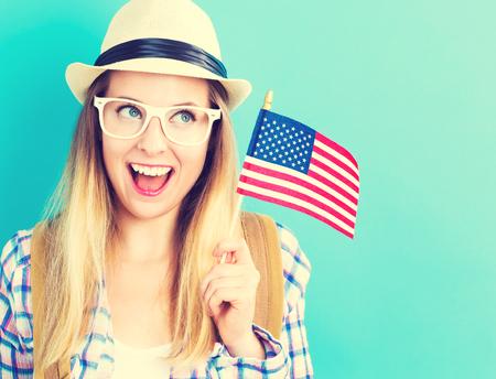 파란색 배경에 미국 국기를 들고 행복 젊은 여행 여자 스톡 콘텐츠
