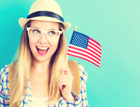 Mujer que viaja joven feliz que sostiene la bandera americana en el fondo azul
