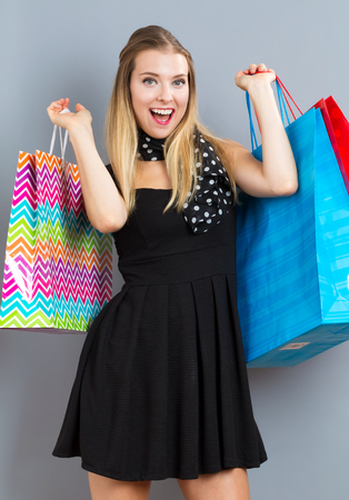 happy shopping: Happy young woman holding many shopping bags on a gray background