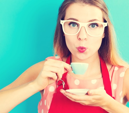 adult woman: Happy young woman drinking coffee on blue background