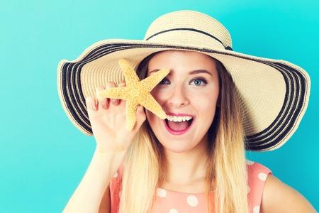 파란색 배경에 불가사리를 들고 행복 한 젊은 여자 스톡 콘텐츠 - 60942108