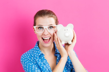Young woman with a piggy bank on pink background