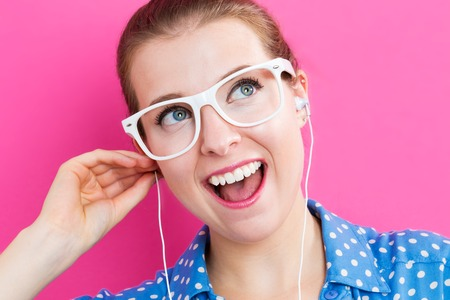 earbuds: Happy young woman with earbuds on pink background Stock Photo