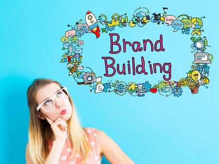 brands: Brand Building concept with young woman on blue background Stock Photo