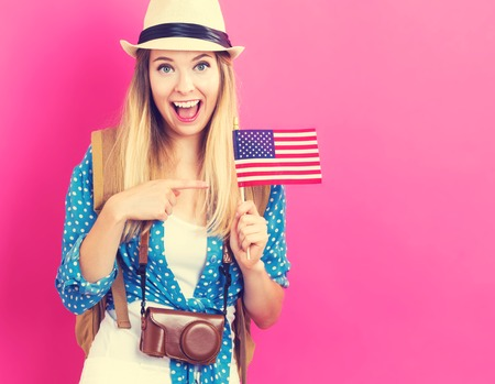 Happy young traveling woman holding American flag on pink background