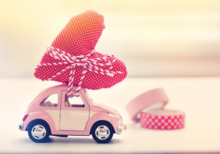 Miniature pink car carrying a heart cushion
