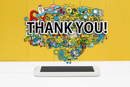 gratefulness: Gracias concepto con el tel�fono inteligente en el fondo de madera de color amarillo