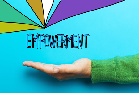 empowerment: Empowerment concept with hand on blue background Stock Photo