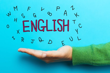 speak: English concept with hand on blue background