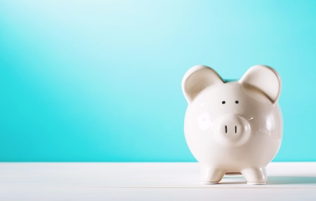 White piggy bank isolated on blue background