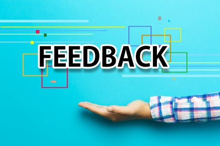 Feedback concept with hand on blue background