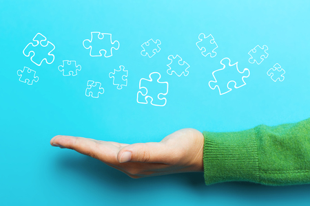 Puzzle concept with hand on blue background Stock Photo
