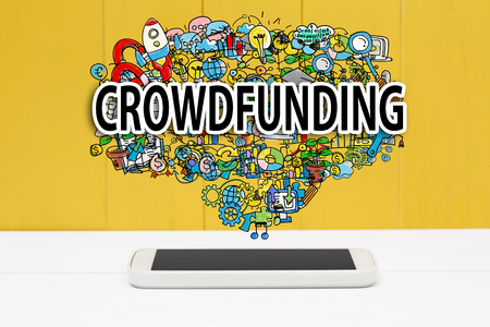 venture: Crowdfunding concept with smartphone on yellow wooden background