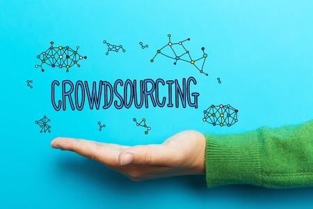 crowd source: Crowdsourcing concept with hand on blue background Stock Photo