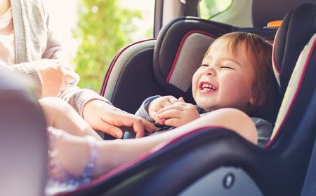 niños sentados: Muchacha del niño abrochado en el asiento del coche