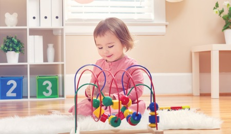 juguete: Happy toddler girl playing with toys in her house