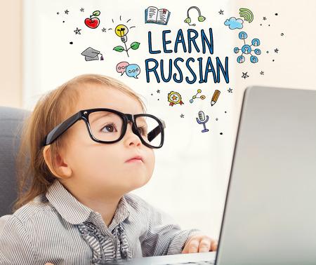랩톱을 사용하는 유아 소녀와 러시아어 개념을 배우십시오.