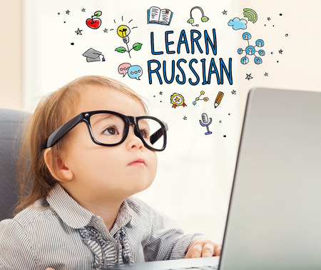 mixed race children: Learn Russian concept with toddler girl using her laptop