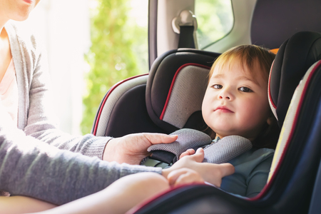 Toddler girl buckled into her car seat