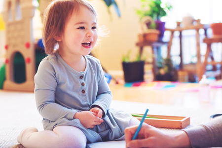 person writing: Happy toddler girl playing in her house