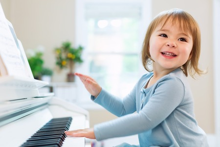 Happy smiling toddler girl excited to play the piano Foto de archivo