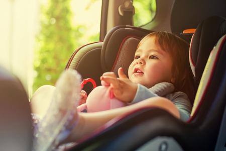 Muchacha del niño abrochado en el asiento del coche Foto de archivo
