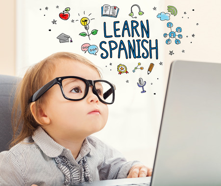 girl laptop: Learn Spanish concept with toddler girl using her laptop Stock Photo