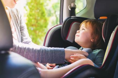 女孩小孩扣上了她的汽車座椅