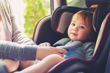 幼児の女の子が彼女の車の座席に座屈