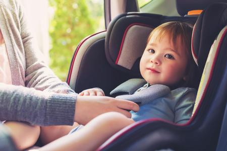 asiento coche: Muchacha del niño abrochado en el asiento del coche