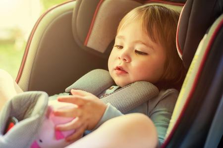 Peutermeisje verbogen in haar autostoeltje Stockfoto