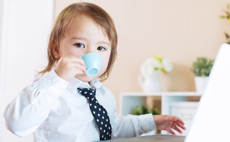 Toddler girl drinking from a coffee mug in front of her laptop