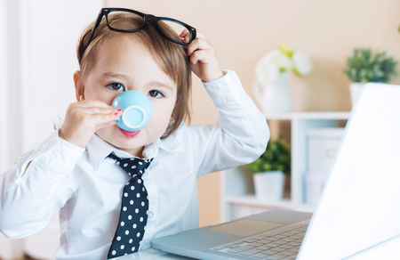 laptop home: Smart little toddler girl with big glasses drinking coffee while using her laptop