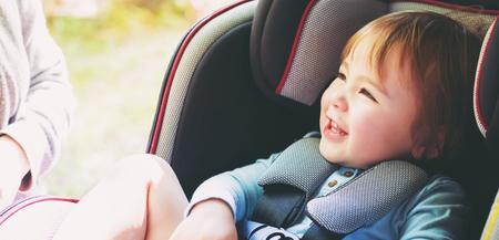 bebe sentado: Muchacha del niño abrochado en el asiento del coche