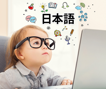mixed race children: Learning Japanese theme with toddler girl using her laptop (text reads - Japanese language) Stock Photo