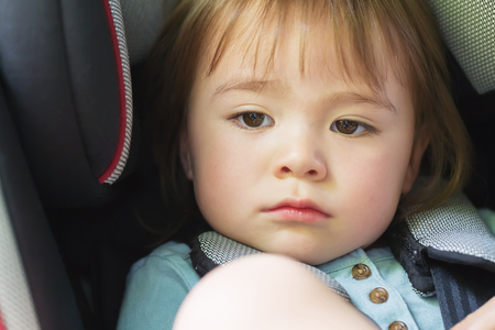 buckled: Toddler girl buckled into her car seat