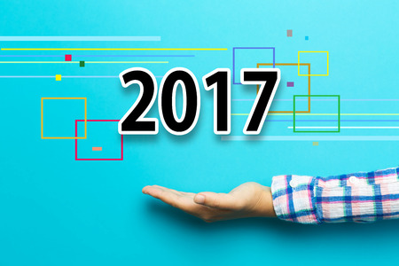 happy new year: 2017 concept with hand on blue background