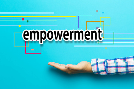 Empowerment concept with hand on blue background Stock Photo