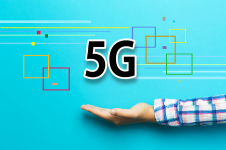 5G concept with hand on blue background
