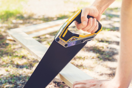 handsaw: Man with a handsaw cutting wood outdoors