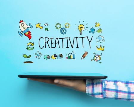 imaginacion: Concepto de la creatividad con una tableta en el fondo azul Foto de archivo