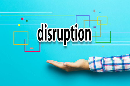 disrupt: Disruption concept with hand on blue background Stock Photo