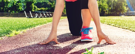 prepare: Female athlete on the starting line of a stadium track preparing for a run Stock Photo