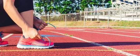 女性ランナーのスタジアム トラックで彼女のスニーカーのひも 写真素材
