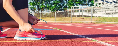 Female runner lacing her sneakers on a stadium running track Stock Photo